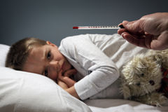 Sick child in bed with high temperature Royalty Free Stock Image