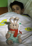 Sick child in bed with teddy bear Royalty Free Stock Images
