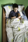 Sick child in bed with teddy bear Royalty Free Stock Photos