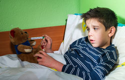 Sick child in bed with teddy bear Stock Photography