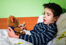 Sick child in bed with teddy bear Stock Images