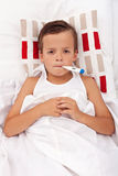 Sick child in bed with thermometer Stock Photo