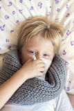 Sick child blowing nose. Sick little child boy blowing nose laying in bed with sad face - healthcare and medicine concept Royalty Free Stock Image