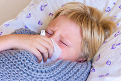 Sick child blowing nose Royalty Free Stock Image