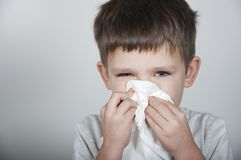 Sick child blows his nose in a handkerchief. On gray background Royalty Free Stock Photo
