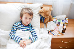 Sick child boy lying in bed with a fever, resting Royalty Free Stock Photography