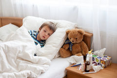 Sick child boy lying in bed with a fever, resting Royalty Free Stock Images