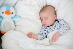 Sick child boy lying in bed with a fever, resting at home. Sick child, baby boy lying in bed with a fever, resting at home stock photo