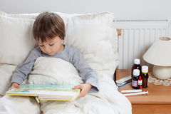 Sick child boy lying in bed with a fever Stock Images