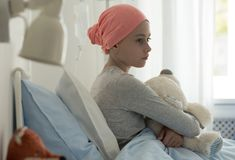 Sick child with cancer sitting in hospital bed