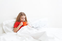 Sick child. Cold sick child laying on bed and drinking a cup of tea Stock Images