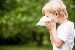 Sick child with a cold sneezing royalty free stock images