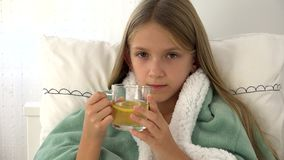 Sick child drinking tea, ill kid in bed, suffering girl, patient in hospital.  stock video footage