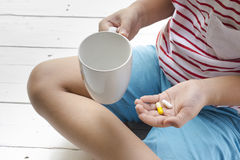 Sick child eating pills with wooden white background .Top view. And close upn Stock Photos
