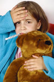 Sick child with fever. Sick child with thermometer in her mouth, a hand on her forehead and clutching a stuffed animal Stock Images