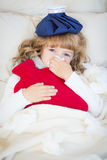 Sick child with fever and hot water bottle. At home Royalty Free Stock Photos