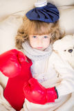 Sick child with fever and hot water bottle. At home Stock Photography