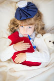 Sick child with fever and hot water bottle. At home Royalty Free Stock Photo