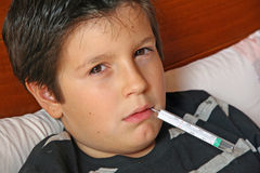 Sick child with a fever and thermometer Stock Photography