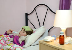 Sick child girl. Lonely sick child girl in a bed Royalty Free Stock Images