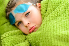 Sick child girl under a blanket Stock Photos