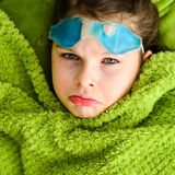 Sick child girl under a blanket Stock Photography