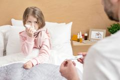 Sick child having a high fever. High fever. Sad sick girl having high fever and blowing her nose Royalty Free Stock Photo