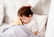 Sick child hugging a teddy bear Stock Photo
