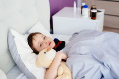 Sick child hugging a teddy bear Stock Image