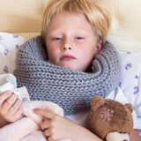 Sick child lying in bed Stock Images