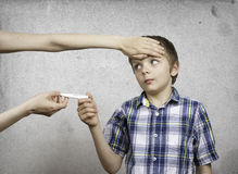 Sick child. Mom gives a thermometer to measure the temperature. Royalty Free Stock Photography