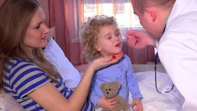 Sick child with mom open mouth and take medicine from male doctor sitting on bed. Static shot. 4K UHD stock footage