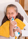 Sick child with nasal spray Royalty Free Stock Image