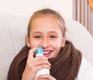 Sick child with nasal spray. Schoolgirl easily using aqua del mar spray indoor Stock Photos