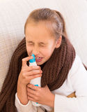 Sick child with nasal spray Stock Image