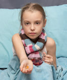 Sick child with pills and a cup of herbal tea Royalty Free Stock Image