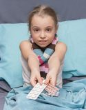 Sick child with pills in hand Stock Photos