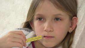 Sick child portrait with thermometer, ill girl in bed, sad kid suffering cold 4K.  stock video footage