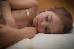 Sick child sleeps. Sick girl sleeps with thermometer stock images