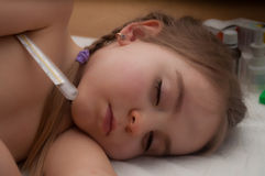 Sick child sleeps. Sick girl sleeps with thermometer royalty free stock image