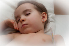Sick child sleeps. Sick girl sleeps with thermometer royalty free stock photography