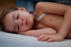 Sick child sleeps. Sick girl sleeps with thermometer Stock Photo