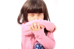 Sick child sneezing. Little sick girl sneezing onto her sleeve because of sickness or allergies Royalty Free Stock Photography