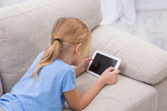 Sick child staying at home palying games on tablet. royalty free stock image