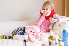 Sick child staying at home. Sick little child sneezing nose while staying at home Stock Photography