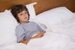 Sick child with thermometer resting in bed Stock Images