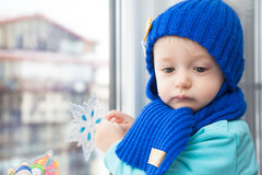 Sick child in warm clothes looking sad during winter holidays in house opposite window, waiting for Christmas Stock Photography