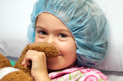 Sick child wearing surgical cap. Sweet sick little girl wearing hospital surgical cap before surgery and holding her toy bear for comfort against stress stock image