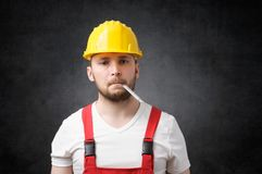 Sick construction worker. With with a thermometer in his mouth Royalty Free Stock Images