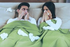 Sick Couple Blowing Noses. Napkins on Sofa. Treatment at Home. Diseas and Illnesses. Sick Man and Woman. Two Sad People. Virus Symptom. Diseases and Fever stock photo